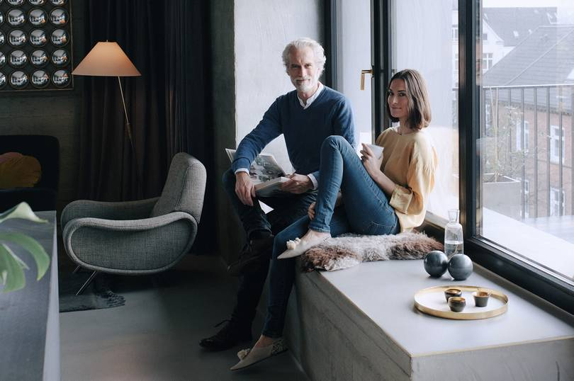 Middle-aged couple sitting on a windowsill in a new flat.