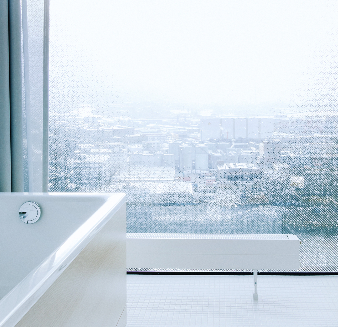 Part of a white bathtub, behind it a floor-level window with a view of Hamburg.