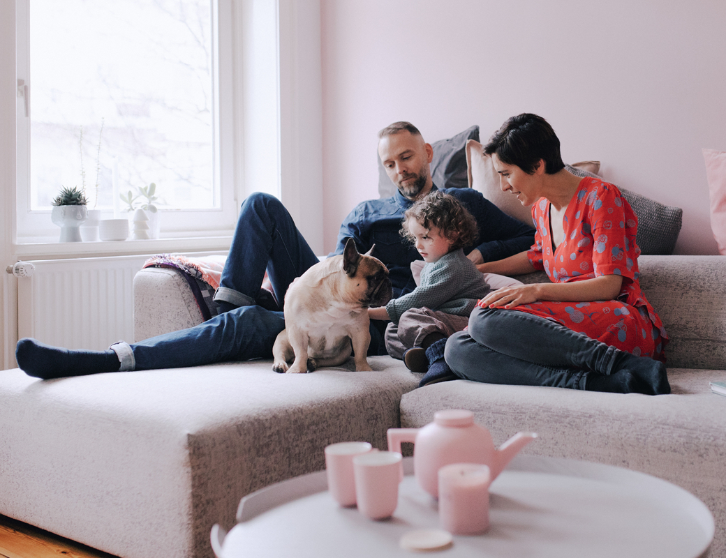 A young family sitting on a sofa with a child and a pug.