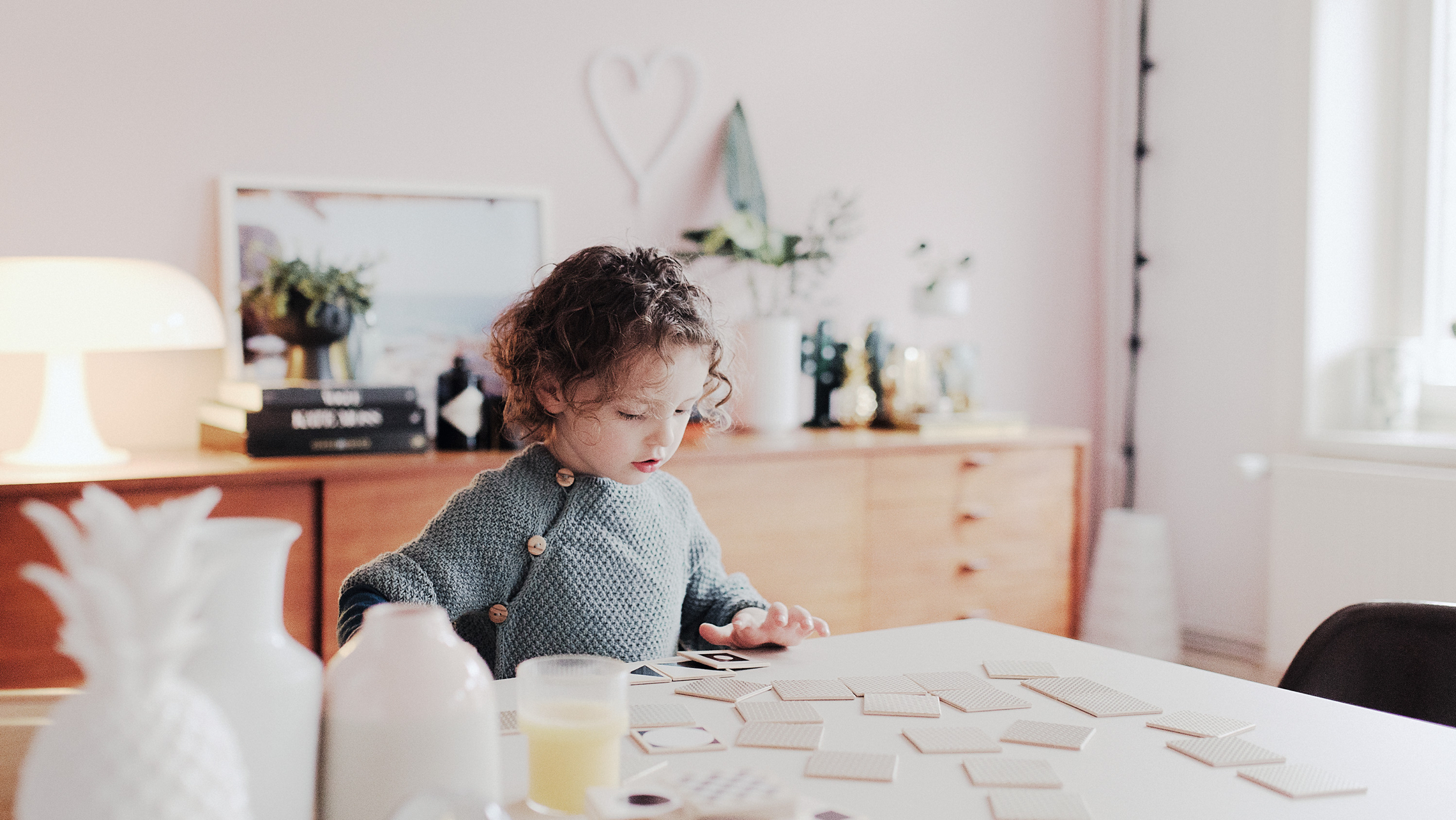 a young child with curly hair sitting at a table with Match Up cards